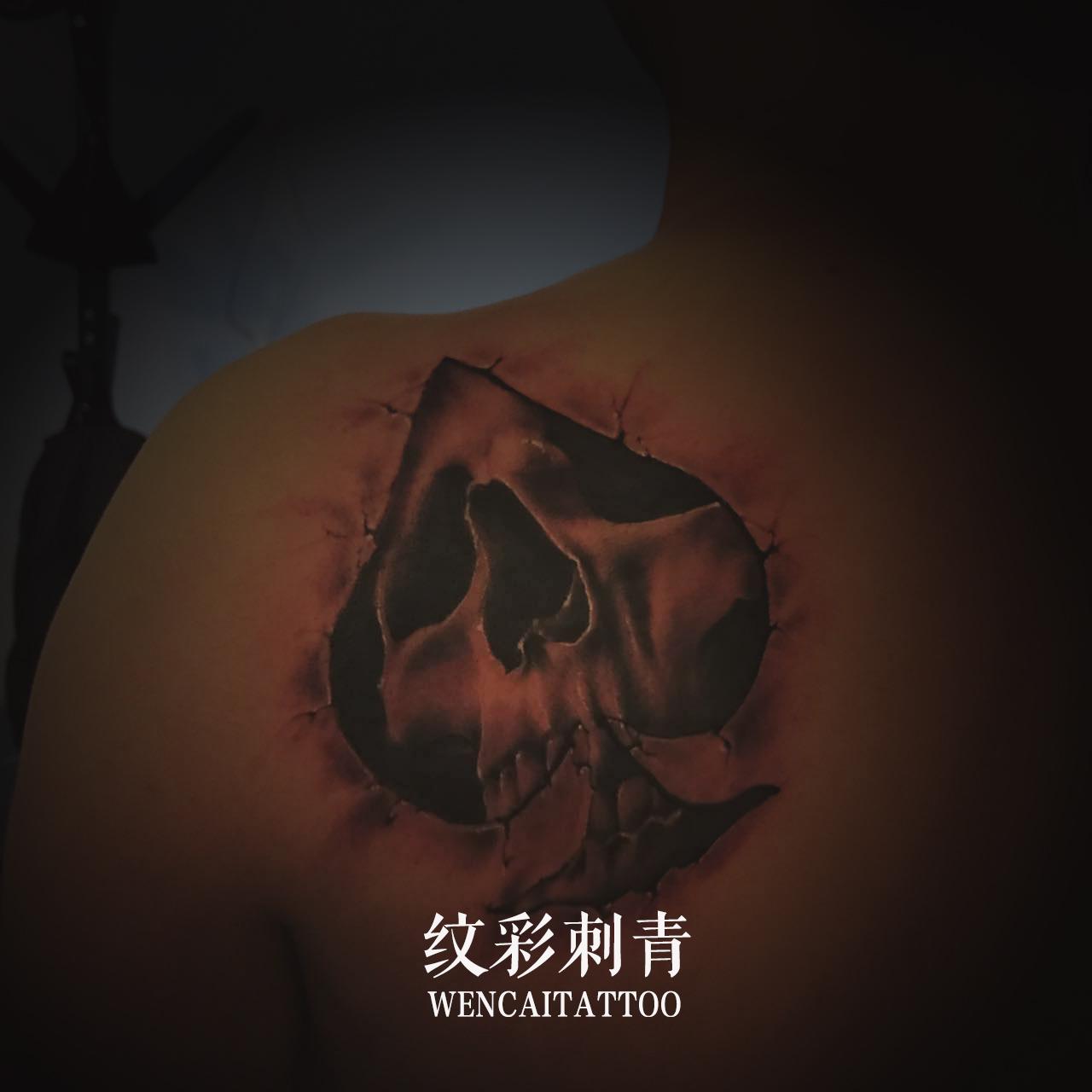 青岛梁先生后背上的黑桃骷髅纹身图案